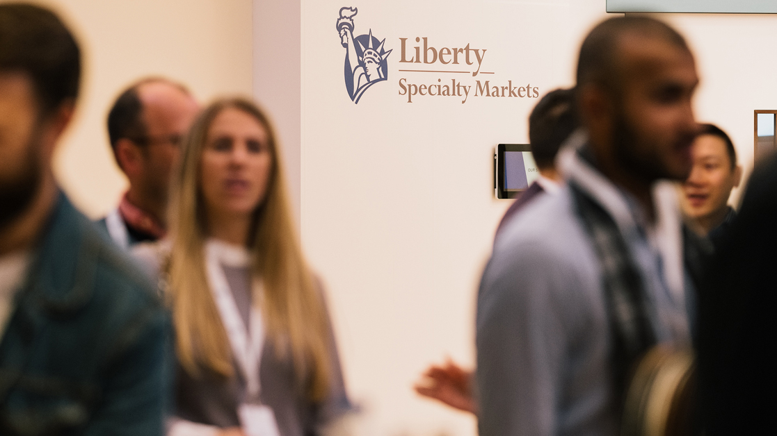 Group of employees walking in front of the Liberty Specialty Markets logo in the office