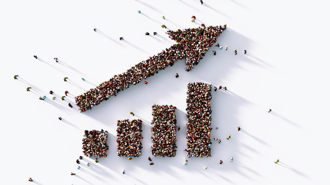Birds eye view of a human crowd forming an upward trending bar graph and arrow