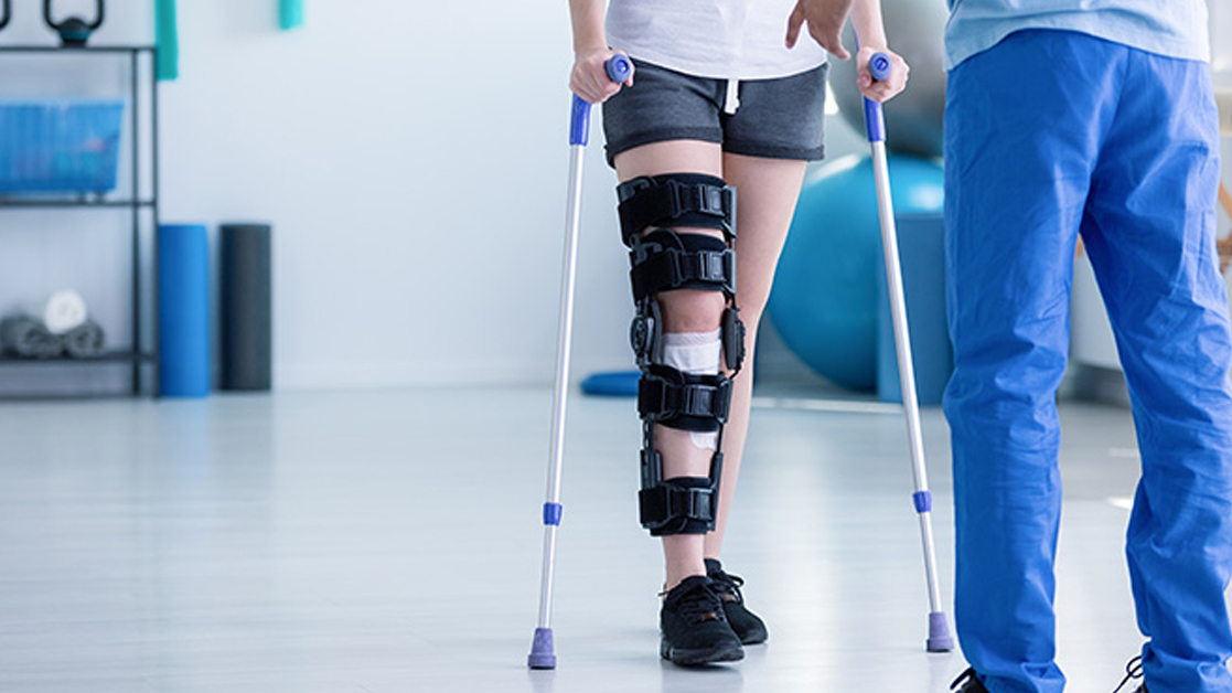Bottom half of patient in a leg brace standing in a medical facility, facing healthcare professional