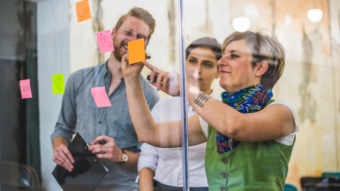 Three business professionals sticking post-it notes to an office wall while working together