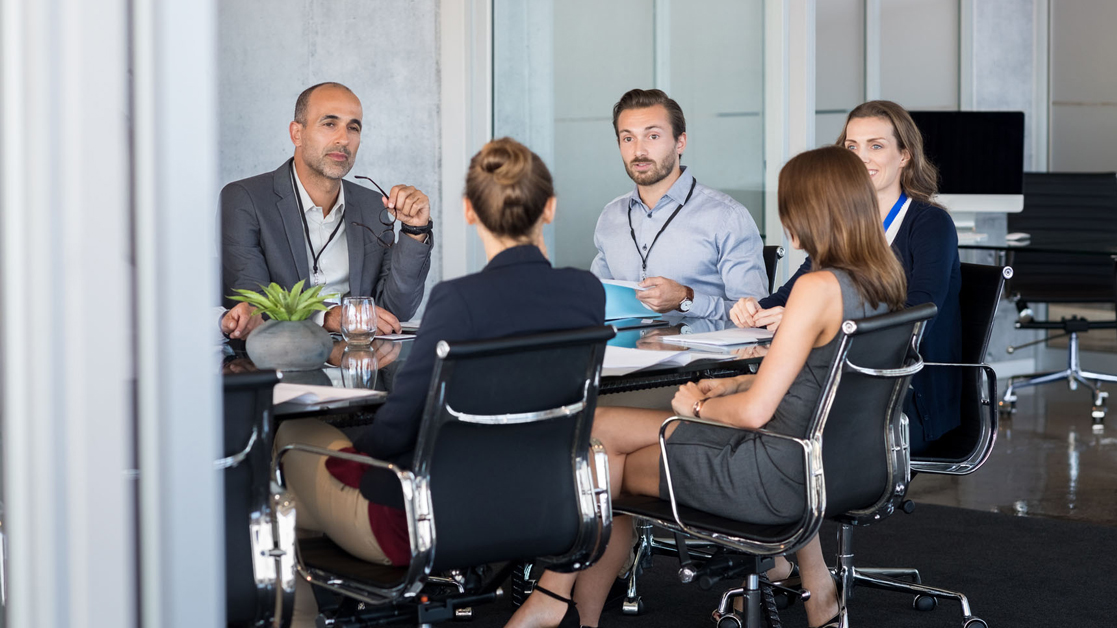 Group of business professionals sitting around a conference table working together