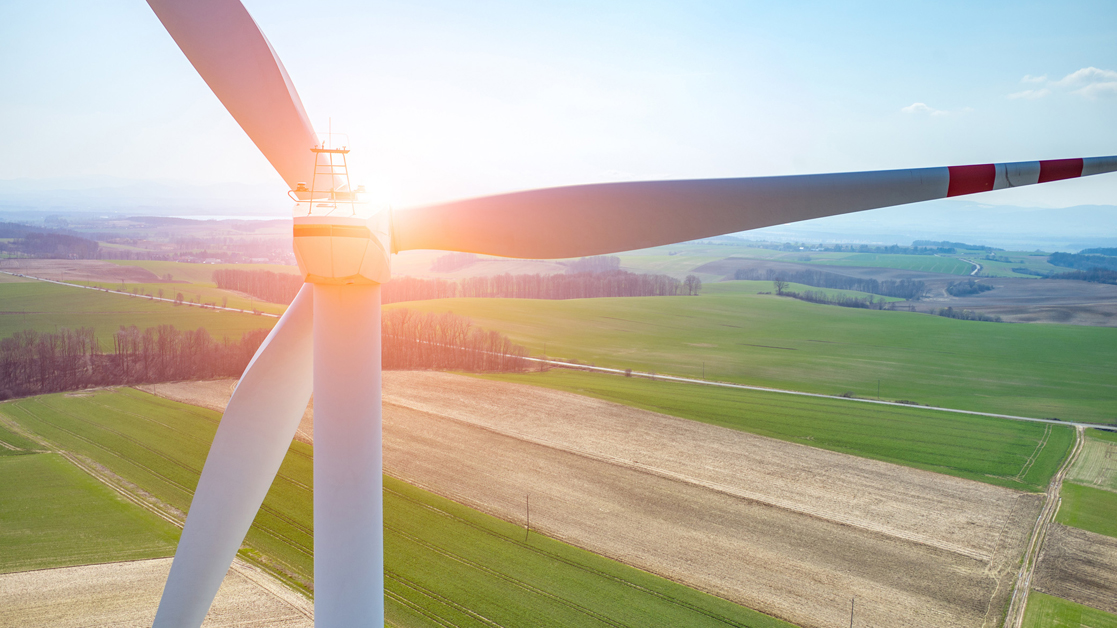 Wind turbine on a large field during sunset