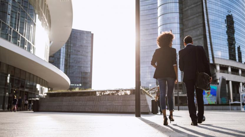 Professional man and woman walking together towards a city office building