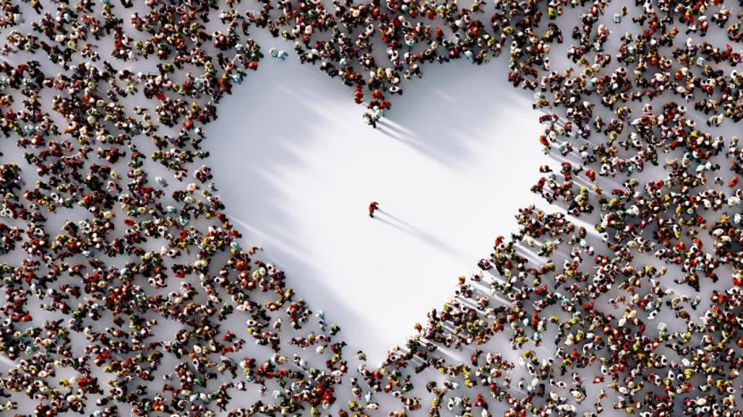 Lone man standing in a white heart shaped void formed by a surrounding crowd