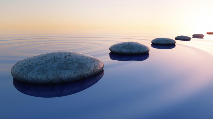 Row of evenly spaced stones resting on calm water