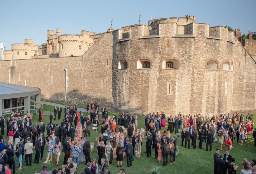 Large group in cocktail attire by the Tower of London at the 2019 summer party