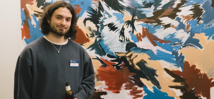Artist standing next to their work